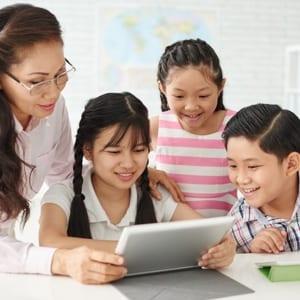 Teacher guiding students on ipad